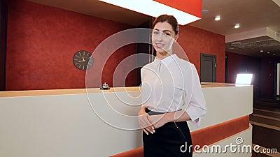 Грациозно женское работник службы рисепшн стоит в лобби и усмехаться гостиницы видеоматериал