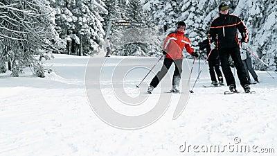 Группа в составе более старые люди наслаждается кататься на лыжах в зиме