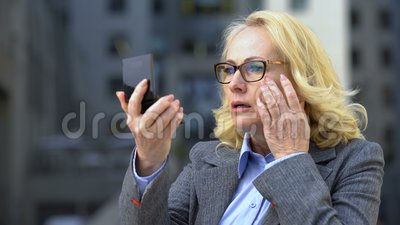 Грустная бизнес-леди смотря морщинки в зеркале руки, против старения косметики глаза акции видеоматериалы