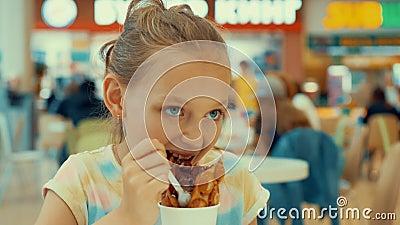 Грустная девушка подростка есть мороженое шоколада в кафе Подросток маленькой девочки есть десерт мороженого с вафлей внутри видеоматериал