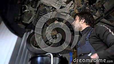 Грязный автоматический механик вывинтить несенный фильтр для масла под поднятым автомобилем во время обслуживания акции видеоматериалы
