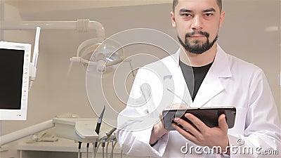 Дантист держит цифровую таблетку видеоматериал