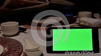 Движение зеленого телефона экрана с людьми нерезкости смотря меню акции видеоматериалы