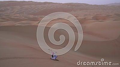 Девочка-подросток свертывает на sandboard на наклоне дюны в отснятом видеоматериале запаса Объединенных эмиратов пустыни Khali al сток-видео