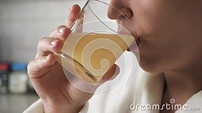 Девочка пьет апельсиновый сок Женские руки приносят стакан апельсинового сока в лицо и пьют его Закрыть видеоматериал