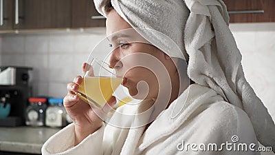 Девочка пьет апельсиновый сок Женщина на кухне в белой халате с полотенцем на голове сидит перед окном и сидит перед окном сток-видео