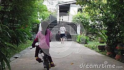 Девочка учится кататься на велосипеде и падает вниз, пока мать идет впереди сток-видео