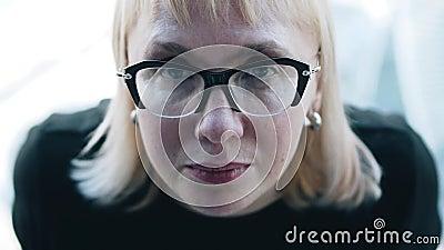 Девушка в очках с глубоким взглядом смотрит на камеру Очень эмоционально и атмосферно видеоматериал