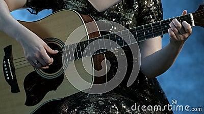 Девушка в платье вечера играет 6-зашнурованную акустическую гитару Правая рука касается строкам, левым владениям руки хорда видеоматериал