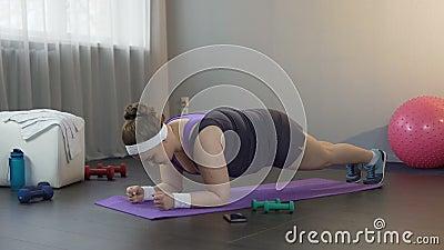 Девушка делая большое усилие стоять в положении планки, работая крепко для того чтобы потерять вес видеоматериал