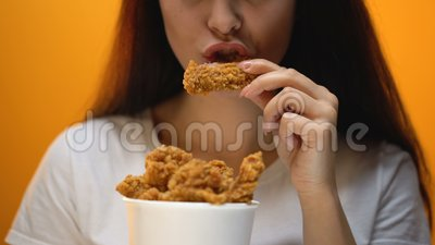 Девушка есть крылья цыпленка, высокую еду калории и риски для здоровья, холестерол акции видеоматериалы