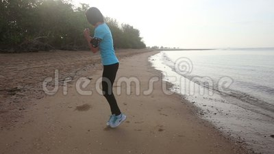 Девушка идет на трот jog вдоль пляжа на восходе солнца акции видеоматериалы
