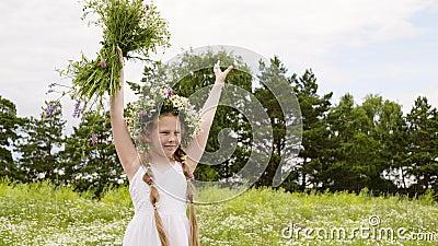 Девушка подростка в венке цветка подняла вверх руки с цветками луга на зеленом поле Счастливое удерживание девушки в руках наверх акции видеоматериалы