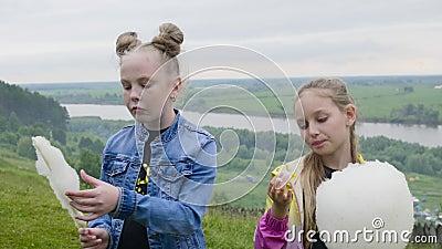Девушка 2 подростков есть сладкий хлопок на ландшафте леса и реки лета Девушки со сладким хлопком представляя для видеоматериал