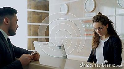 Девушка работник службы рисепшн на в гостинице разговаривая с приезжанным бизнесменом о регистрации и давая ключевую карточку к ч сток-видео