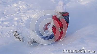 Девушка свертывает вниз холм в санях Снег летает к ребенку в стороне, счастливых играх девушки в парке в зиме движение медленное сток-видео