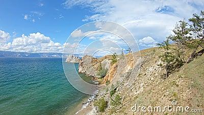 Девушка сидя на скале и рисует Трутень летает над скалистым берегом Lake Baikal акции видеоматериалы