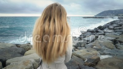 Девушка стоит на пляже во время шторма на море акции видеоматериалы