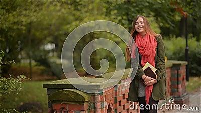 Девушка студента держа книги нося идти рюкзака внешний усмехаясь счастливый в парк Кавказский женский коллеж или акции видеоматериалы