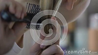 Девушка школы расчесывая щетку волос пластичную, режим красоты, женственность, заботу тела видеоматериал