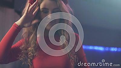 Девушка Dj в красном платье закручивая на turntable в ночном клубе совершитель танцулька cheer сток-видео