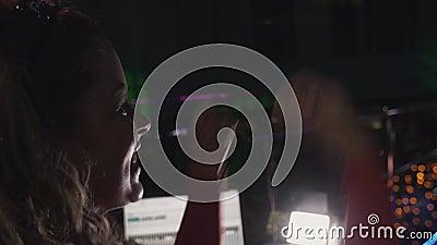 Девушка Dj в красных руках повышения платья на turntable на партии в ночном клубе бить видеоматериал