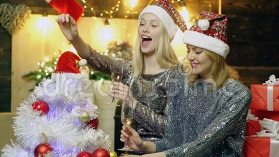 Девушки в шляпах рождества украшают рождественскую елку и выпивают шампанское на предпосылке украшений рождества ново видеоматериал
