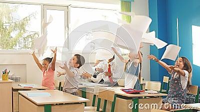 Дети школы имеют потеху в классе и бросая бумаге в воздухе акции видеоматериалы