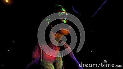 Длинношерстая девушка с цветным флуоресцирующим отпечатком на коже сток-видео