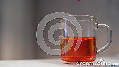 Добавить в воду оранжевый цвет пищи на сером фоне Разноцветный краситель в прозрачной стеклянной кружке акции видеоматериалы