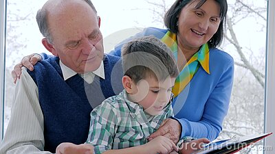 Домашнее образование, ребенок с дедами прочитало книгу на отдыхе сток-видео