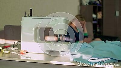 Дом швейной машины на таблице workplace На заднем плане, белошвейка смотрит в смартфон сток-видео