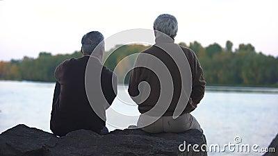 Достигшие возраста мужские друзья сидя совместно снаружи, смотрящ горизонт реки, безмятежность сток-видео