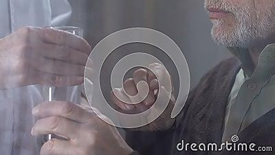 Достигший возраста человек принимая таблетки от докторов вручает, надлежащая внимательность в доме престарелых акции видеоматериалы