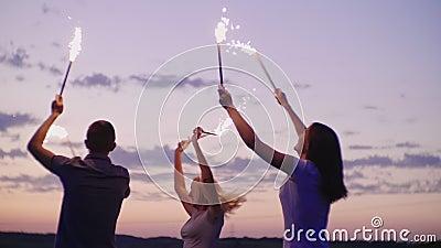 Друзья имеют потеху в фейерверках Через после заход солнца, партия пляжа видео замедленного движения акции видеоматериалы