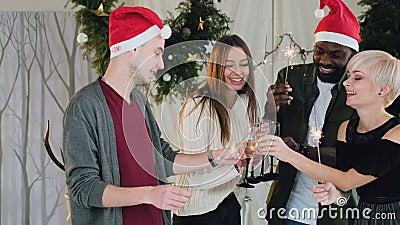 Друзья празднуют Новый Год в белой комнате с украшениями рождества рядом с красивой рождественской елкой привлекательностей видеоматериал
