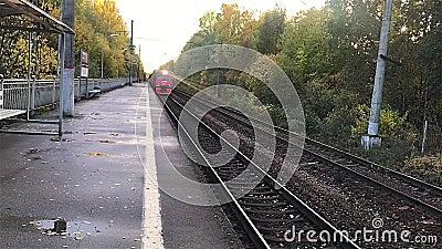 Железнодорожная линия на фоне осеннего ландшафта Российский железнодорожный электрический поезд приближается к станции и останавл акции видеоматериалы