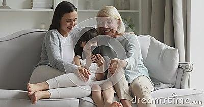 Женская семья, состоящая из нескольких поколений, развлекается с помощью смартфона видеоматериал