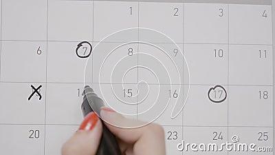 Женские руки с красными датами маникюра объезжая и пересекая на календаре рисуя дни унылые стороны на период используя черную руч видеоматериал