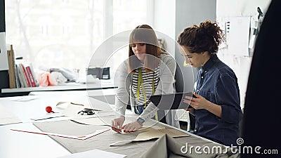 Женские сотрудники шить студии работают с картинами и тканью, конспектируют вырез, говорят и используют таблетку сток-видео