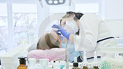 Женский дантист с ассистентом рассматривает рот пациента человека достигшего возраста человека r сток-видео