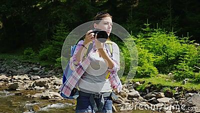 Женский фотограф фотографирует природа В живописном месте на заднем плане леса около горы сток-видео