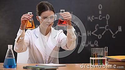 Женский химик показывая жидкости в склянках к камере, превращаясь новому веществу сток-видео