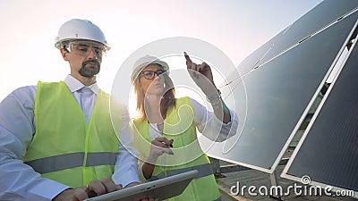 Женское и мужские солнечные контролеры имеет обсуждение около солнечного модуля Зеленая концепция энергии сток-видео
