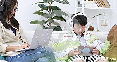 Женщина в стеклах сидя на софе используя компьтер-книжку дома на живущей предпосылке для работы крыто видеоматериал