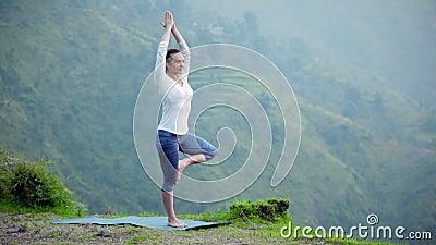 Женщина делая представление дерева asana йоги outdoors видеоматериал
