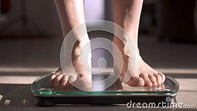 Женщина измеряя ее вес используя масштабы на деревянном поле диетпитание здоровое видеоматериал