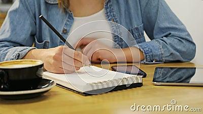 Женщина конца-вверх вручает держать smartphone и запись в тетради в кафе с деревянной мебелью сток-видео