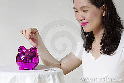 Женщина кладя монетку в коробку денег