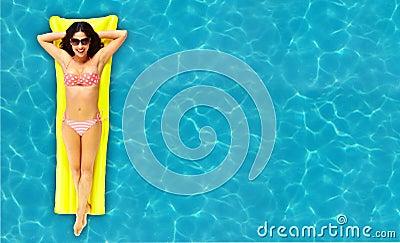 Женщина ослабляя в бассейне.